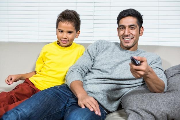 Glimlachende vaderans zoon die op tv op de bank let