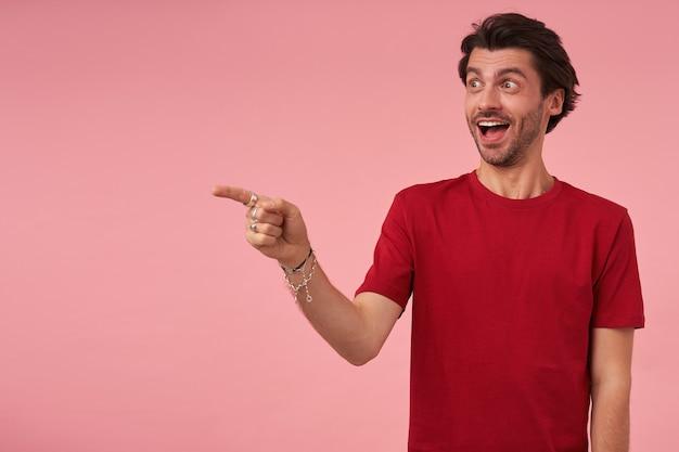 Glimlachende verbaasde jonge man met stoppels in rode t-shirt wijzend naar copyspace met wijsvinger en kijkend naar de zijkant