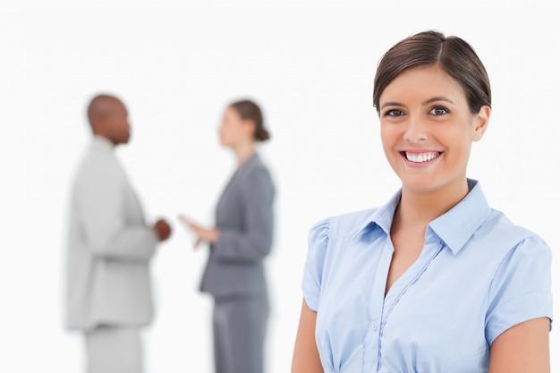 Glimlachende verkoopster met sprekende collega's achter haar