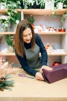 Glimlachende verkoper die de doos van de gift in inpakpapier, decoratieproces verpakken. vrouw wraps aanwezig op tafel, decorprocedure