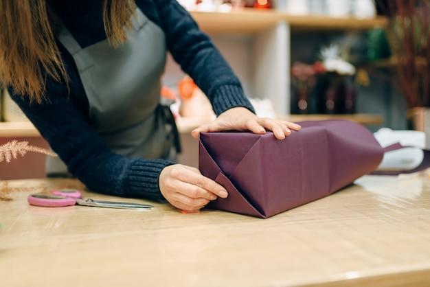 Glimlachende verkoper die de doos van de gift in inpakpapier verpakken