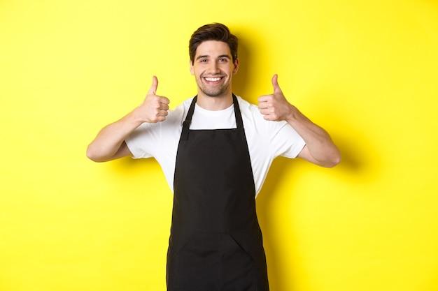 Glimlachende verkoper in zwarte schort die duimen toont, keurt of houdt van iets, adviseert koffie of winkel, gele achtergrond.
