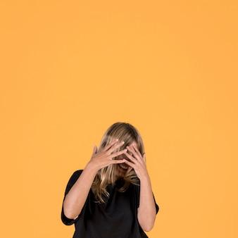 Glimlachende verlegen vrouw die haar gezicht behandelt met vinger