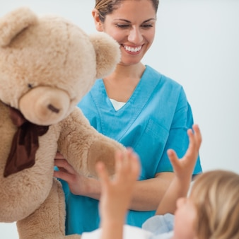 Glimlachende verpleegster die een teddybeer houdt