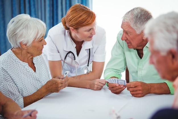 Glimlachende verpleegster die hogere persoon tijdens een spel van kaarten bekijkt