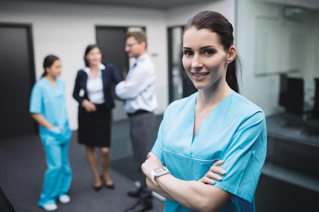 Glimlachende verpleegster die zich met gekruiste wapens bevindt
