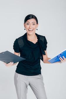Glimlachende verraste bedrijfsvrouw die een omslag met documenten op een grijze achtergrond houdt
