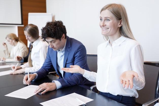 Glimlachende verwarde werkneemster haalt schouders op tijdens zakelijke bijeenkomst