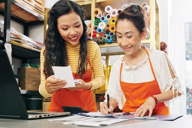 Glimlachende vietnamese bloemisten die rekeningen en kassabonnen controleren en de boekhouding netjes houden