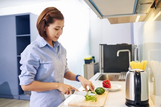 Glimlachende vietnamese huisvrouw die paprika's snijdt voor salade bij het koken van diner