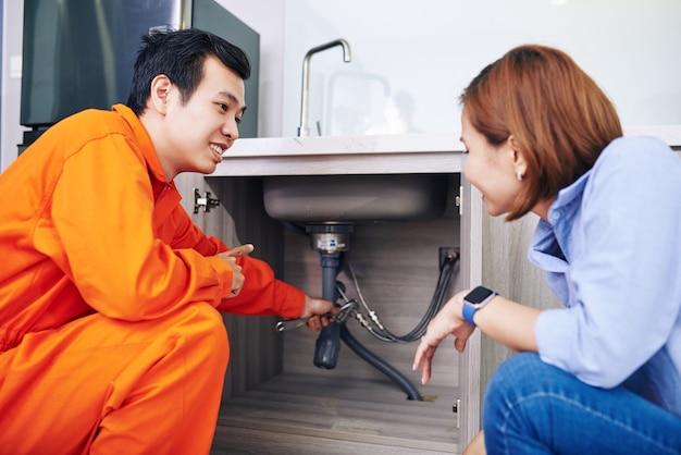 Glimlachende vietnamese loodgieter die vaste of geïnstalleerde pijpen onder gootsteen in keuken van jonge vrouw toont