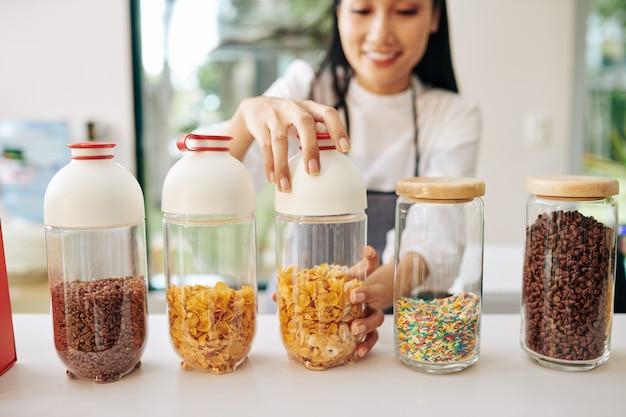Glimlachende vietnamese ober die container met cornflakes opent om ontbijt voor klant te maken