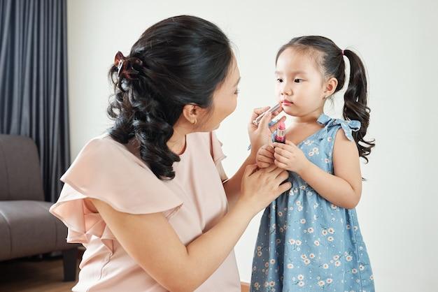 Glimlachende vietnamese vrouw die lichtroze hydraterende lippenbalsem op de lippen van haar dochtertje toepast