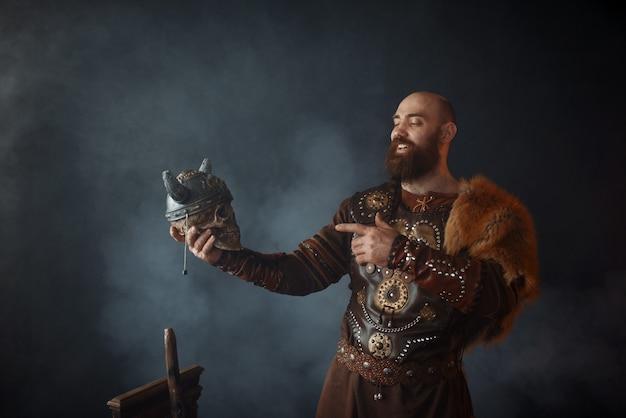 Glimlachende viking gekleed in traditionele scandinavische kleding houdt de schedel van de vijand in helm