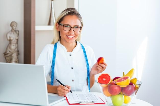 Glimlachende voedingsdeskundige die in bureau een fruit houdt