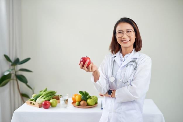 Glimlachende voedingsdeskundige in haar kantoor, ze houdt een groene appel vast en toont gezonde groenten en fruit, gezondheidszorg en dieetconcept