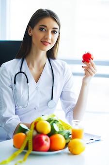 Glimlachende voedingsdeskundige in haar kantoor