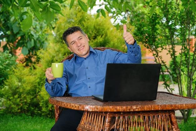 Glimlachende volwassen blanke man die koffie drinkt en duim met vingers laat zien aan zakenpartner via laptop in huistuin. bedrijfsconcept op afstand