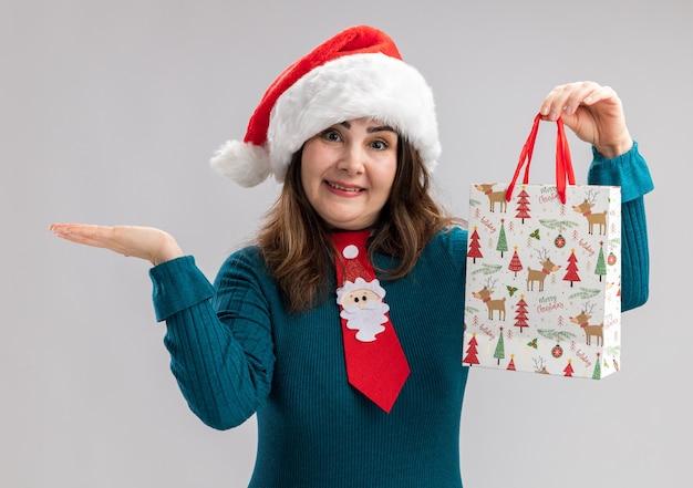 Glimlachende volwassen blanke vrouw met kerstmuts en santa stropdas papier geschenkdoos te houden en hand open te houden geïsoleerd op een witte achtergrond met kopie ruimte