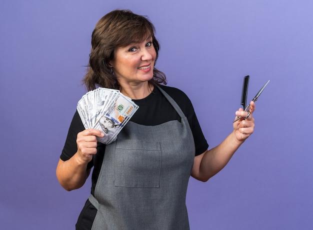 Glimlachende volwassen blanke vrouwelijke kapper in uniform aanhouden van geld kam en schaar geïsoleerd op paarse achtergrond met kopie ruimte