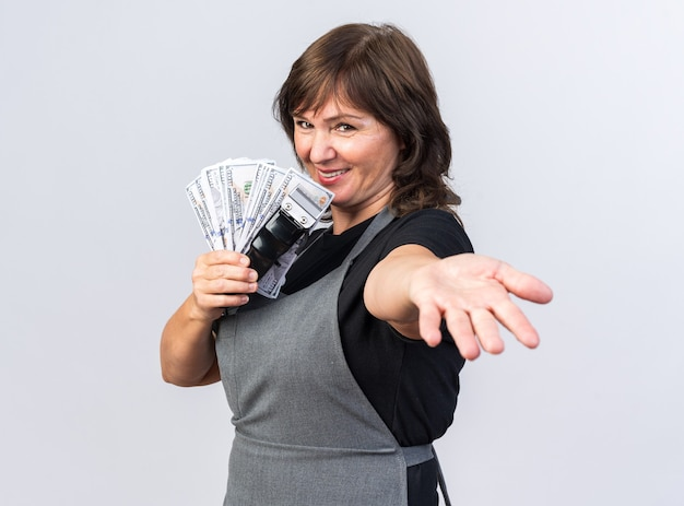 Glimlachende volwassen blanke vrouwelijke kapper in uniform die tondeuse met geld vasthoudt en de hand uitstrekt geïsoleerd op een witte muur met kopieerruimte