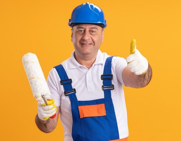Glimlachende volwassen bouwersmens in uniform die beschermende handschoenen draagt ?? duimen omhoog en houdt rolborstel geïsoleerd op oranje muur