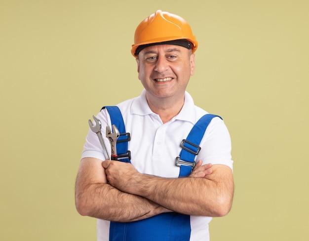 Glimlachende volwassen bouwersmens in uniform staat met gekruiste armen die moersleutel en aapmoersleutel houden die op olijfgroene muur wordt geïsoleerd
