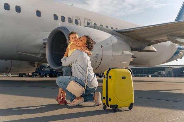 Glimlachende volwassen dame knuffelen haar kind in de buurt van het vliegtuig buiten