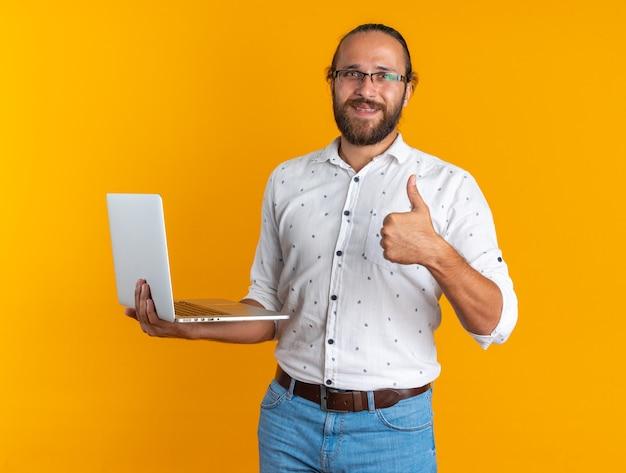 Glimlachende volwassen knappe man met een bril die een laptop vasthoudt en naar een camera kijkt die duim omhoog laat zien op een oranje muur