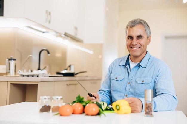 Glimlachende volwassen man bereidt zich voor om de groenten te hakken om een veganistisch gerecht te koken