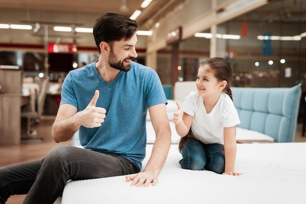 Glimlachende volwassen man en meisje op bed in winkel