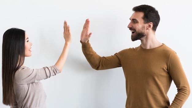 Glimlachende volwassen man en vrouw klaar tot hoogte vijf