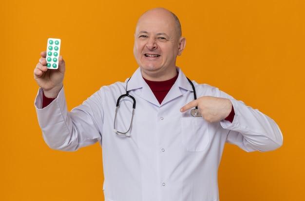 Glimlachende volwassen man in doktersuniform met stethoscoop die medicijnblisterverpakking vasthoudt en naar zichzelf wijst