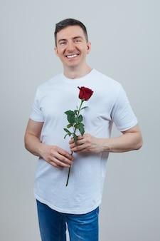 Glimlachende volwassen man in een wit t-shirt met een rode roos in zijn handen. fijne valentijnsdag.