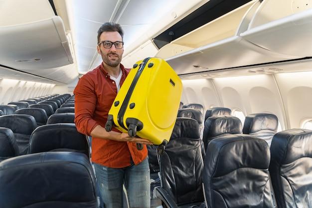 Glimlachende volwassen man met een koffer in het gangpad van een vliegtuig