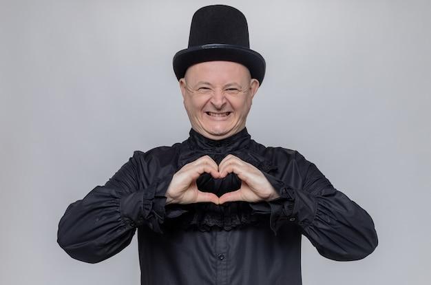Glimlachende volwassen man met hoge hoed en in zwart gotisch shirt gebarend hartteken op zoek