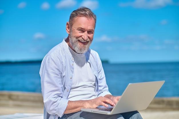 Glimlachende volwassen man met laptop in de natuur