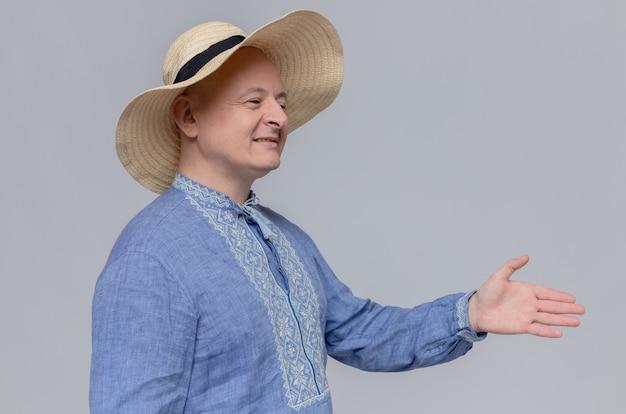 Glimlachende volwassen man met strohoed en in blauw shirt die zijn hand uitsteekt
