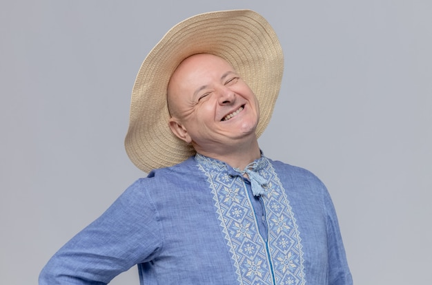 Glimlachende volwassen man met strohoed en in blauw shirt op zoek