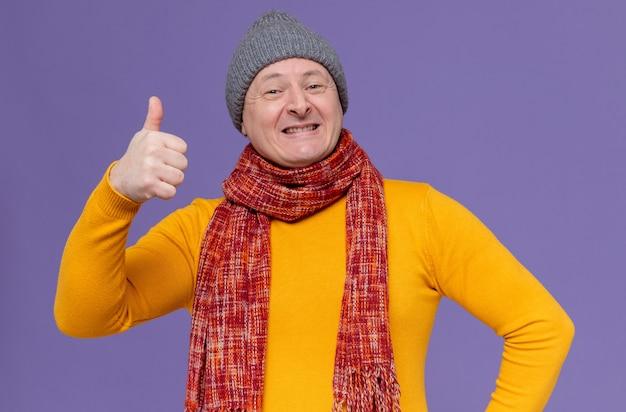 Glimlachende volwassen man met wintermuts en sjaal om zijn nek duimen omhoog