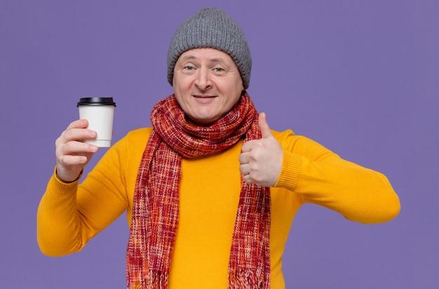 Glimlachende volwassen man met wintermuts en sjaal om zijn nek met papieren beker en duimen omhoog