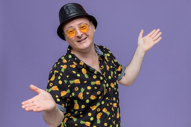 Glimlachende volwassen man met zwarte hoge hoed die een zonnebril draagt die de handen open houdt