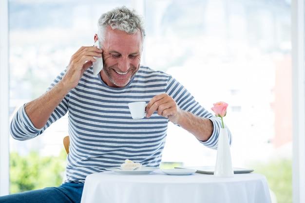 Glimlachende volwassen man praten over de telefoon terwijl het hebben van koffie