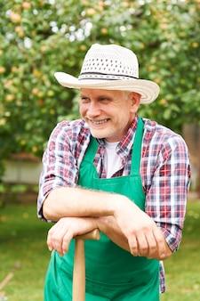 Glimlachende volwassen man tijdens tuinwerk