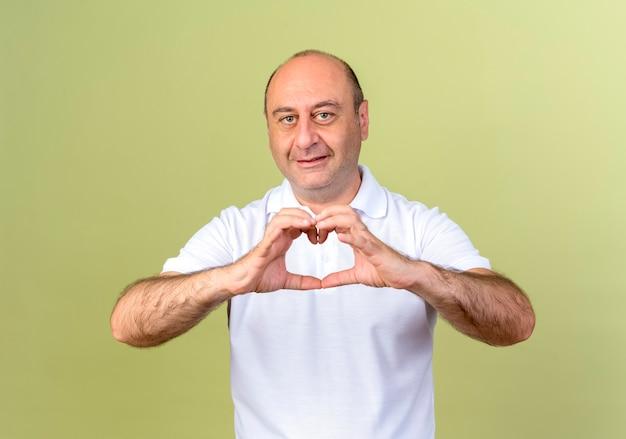 Glimlachende volwassen mens die hartgebaar toont dat op olijfgroene muur wordt geïsoleerd