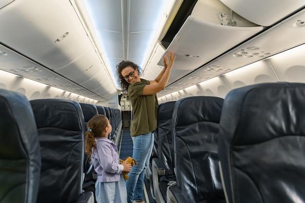 Glimlachende volwassen moeder en kind die voor de vlucht in het vliegtuig staan