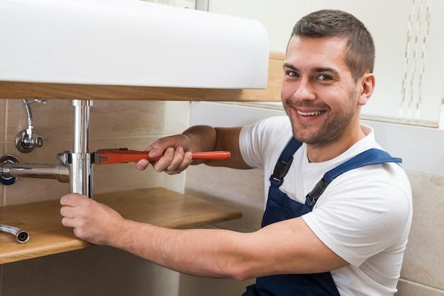 Glimlachende volwassen sanitaire technicus met moersleutel