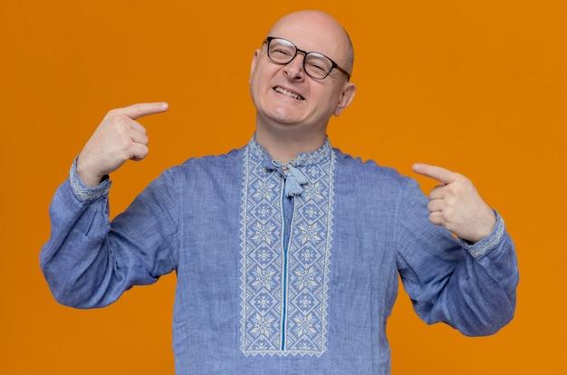 Glimlachende volwassen slavische man in blauw shirt en met optische bril die naar zichzelf wijst