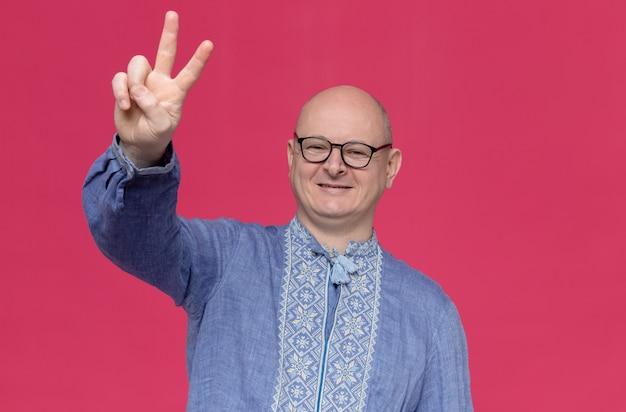 Glimlachende volwassen slavische man in blauw shirt met optische bril die overwinningsteken gebaart