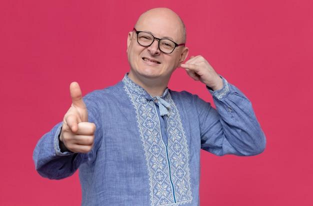 Glimlachende volwassen slavische man in blauw shirt met optische bril gebaren bel me teken en wijzend naar voren